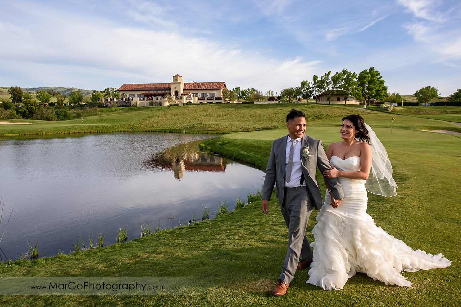 bride and groom with reception hall at Poppy Ridge Golf Course in Livermore