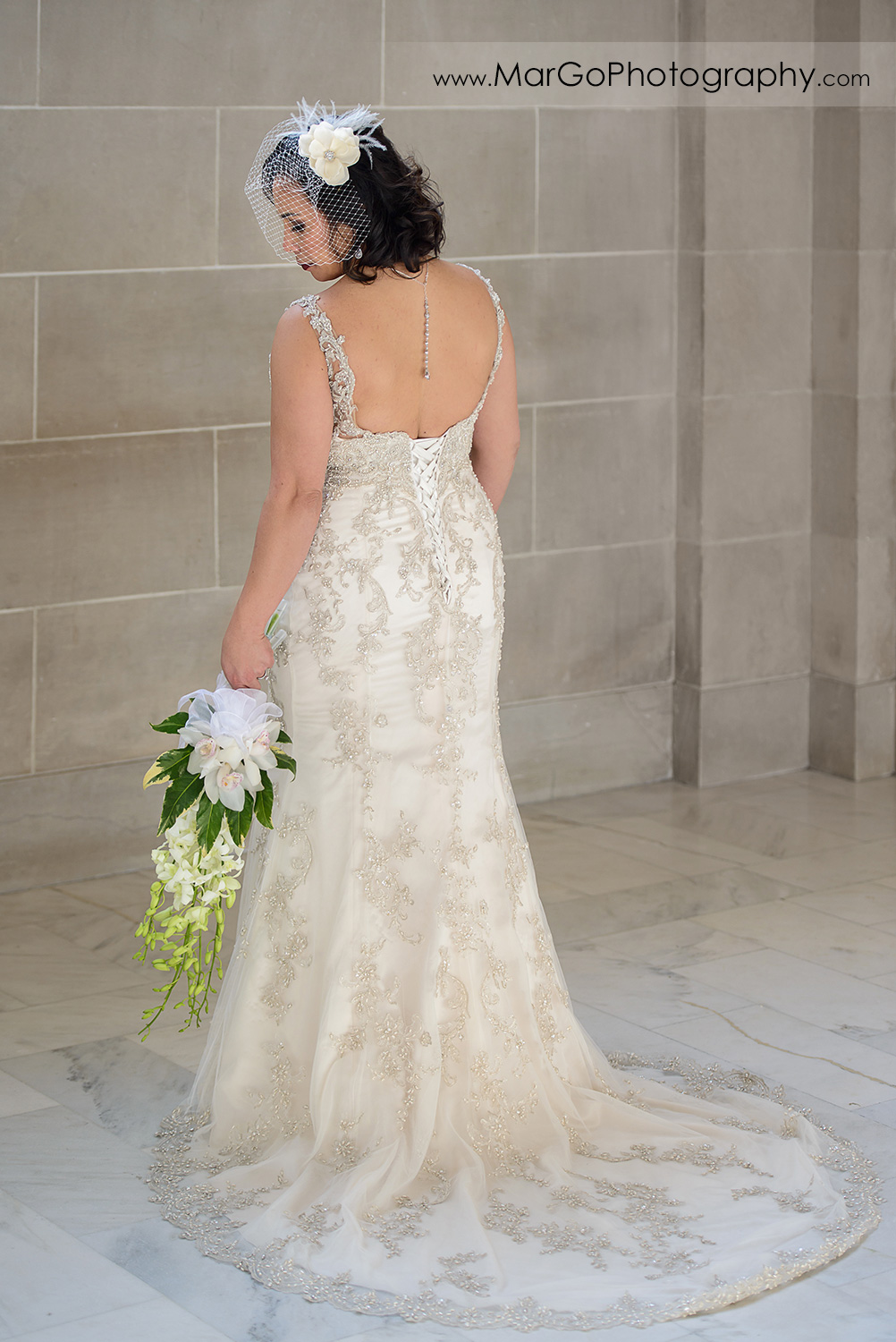 bride looking the bouquet at San Francisco City Hall