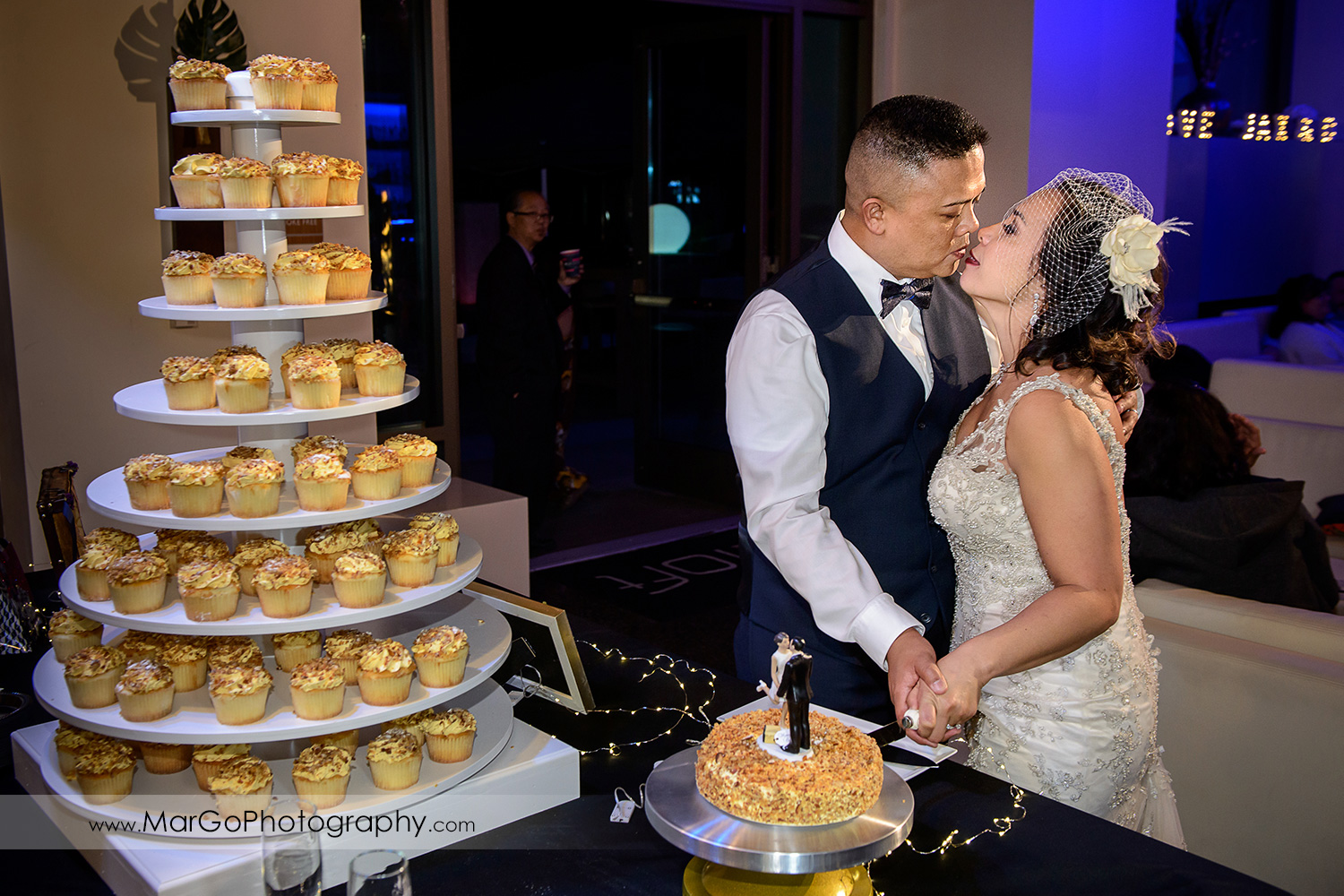 bride and groom kissing during cake cutting at Aloft in Cupertino
