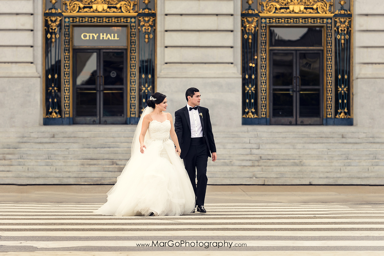 bride and groom on the street in front of San Francisco City Hall