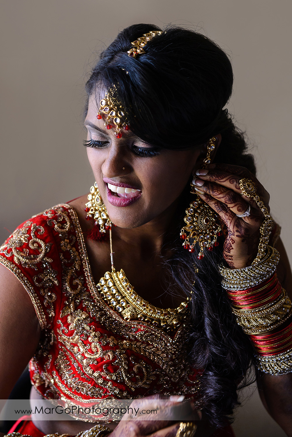 indian bride putting on the earrings at Hotel Shattuck Plaza in Berkeley