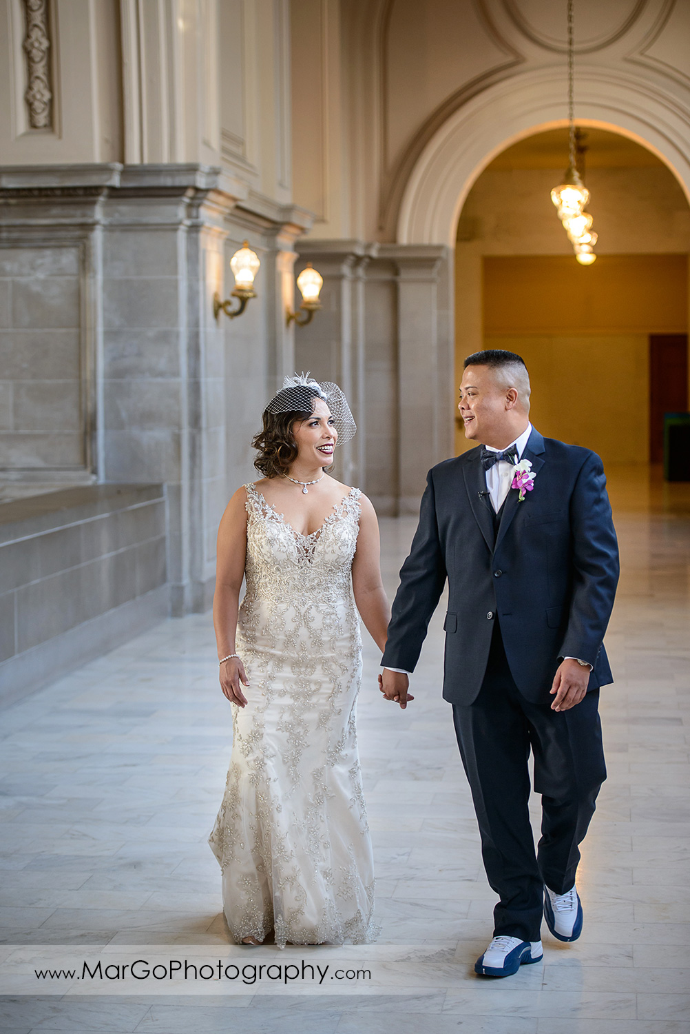 bride and groom walking at San Francisco City Hall