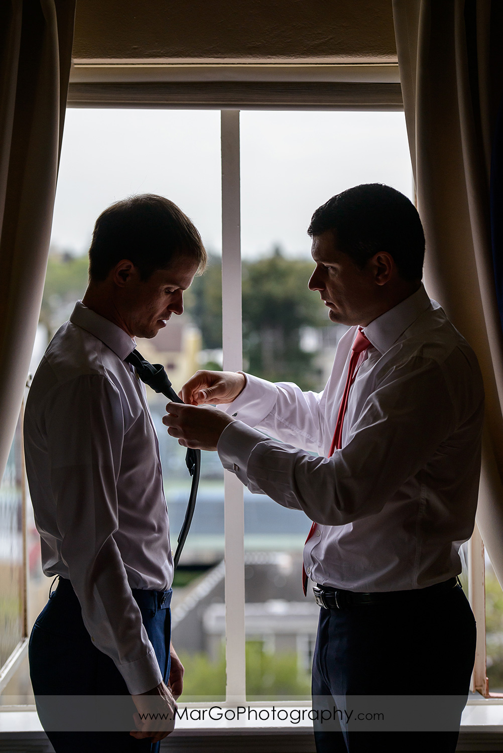 groom and best man getting ready in front of the window at Berkeley City Club