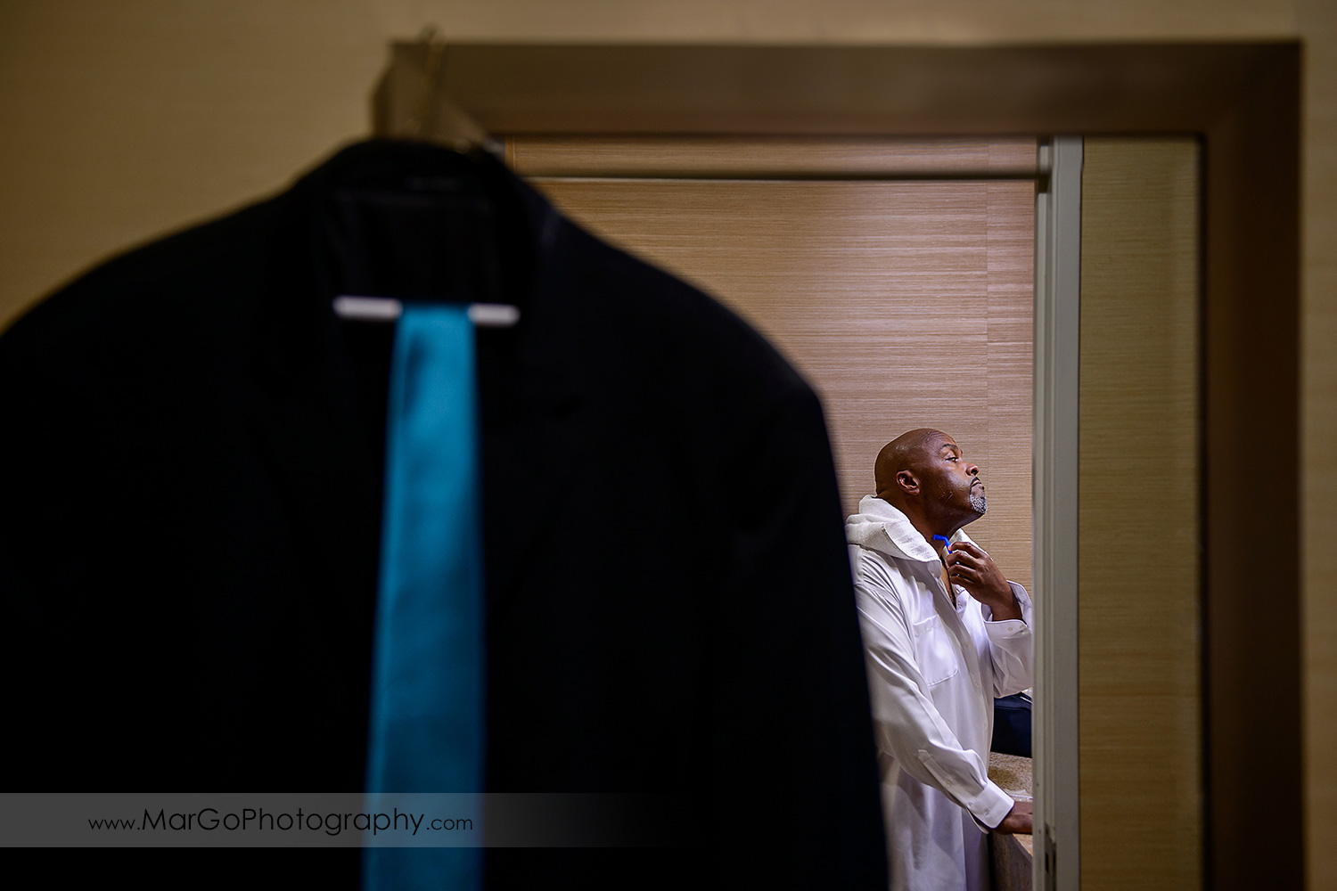 groom getting ready through the hanging jacket at Best Western Plus Delta Inn & Suites in Oakley
