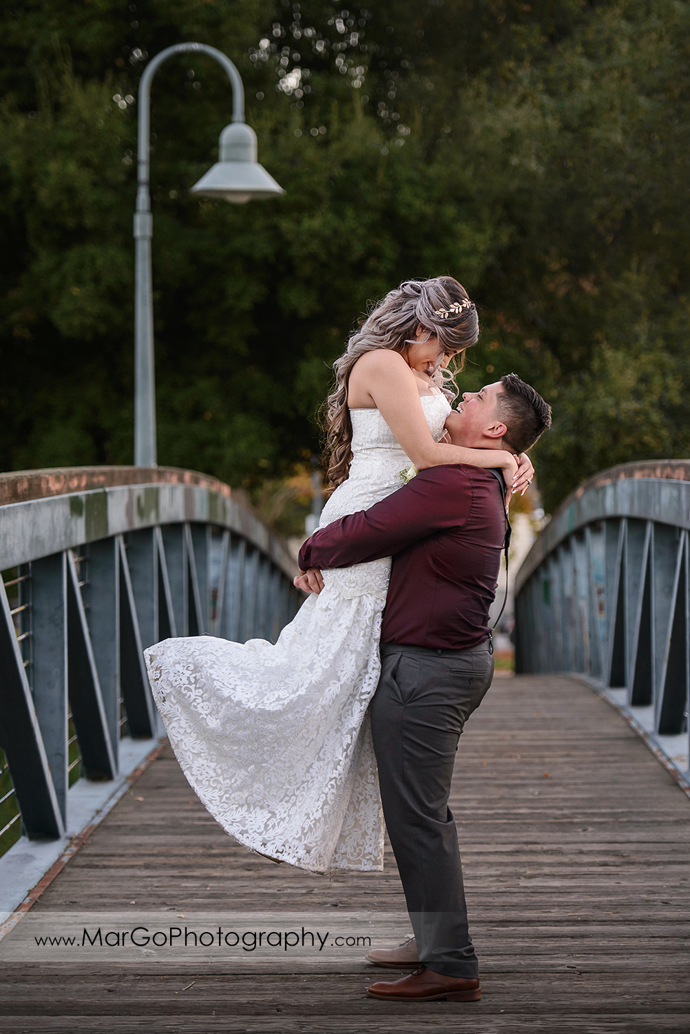 groom lifting the bride on the bridge in Martinez