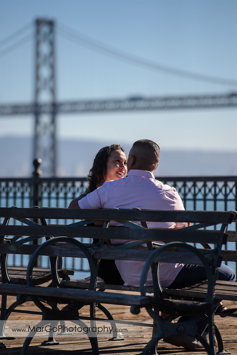 engagement session at Pier 7 in San Francisco - couple on the bench with the Bay Bridge in the background