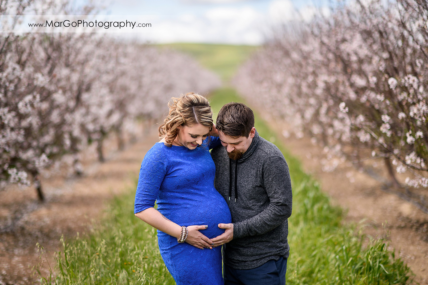 portrait of pregnant couple looking at the belly, Tracy orchard maternity session