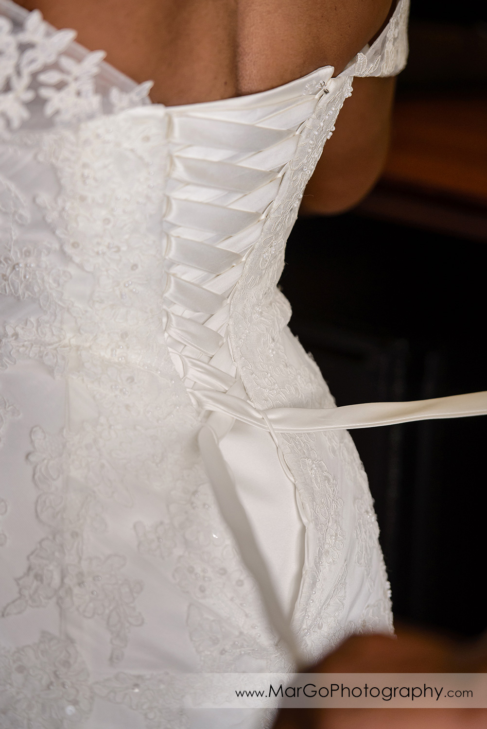 lacing up the wedding dress at Best Western Plus Delta Inn & Suites in Oakley