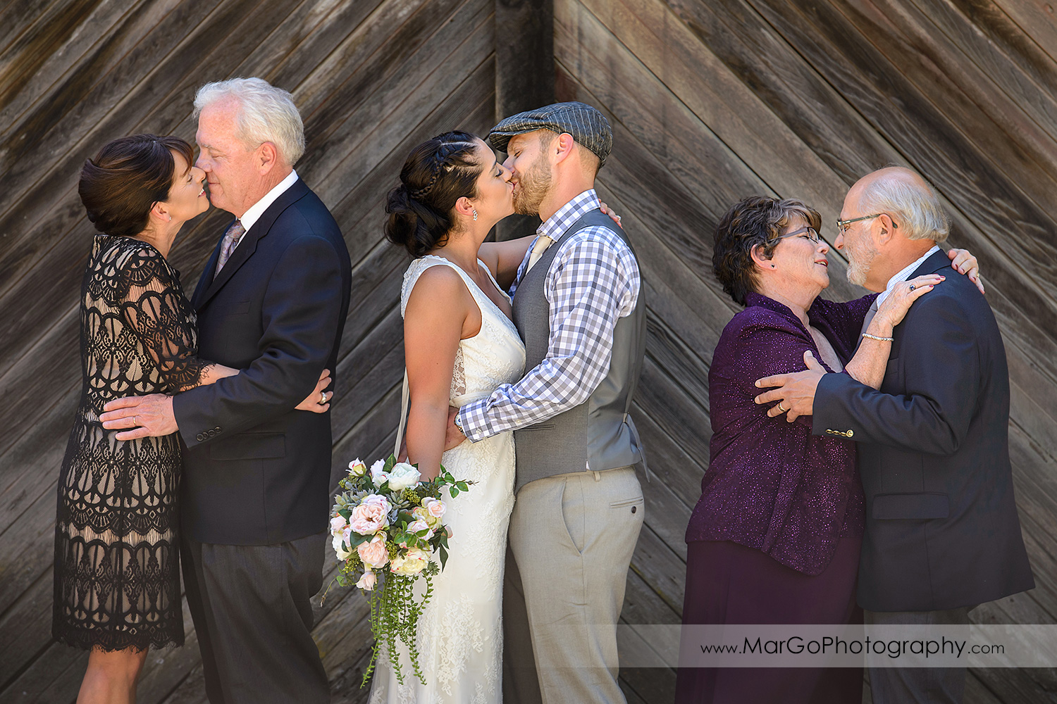 bride, groom and parents kissing at Picchetti Winery in Cupertino