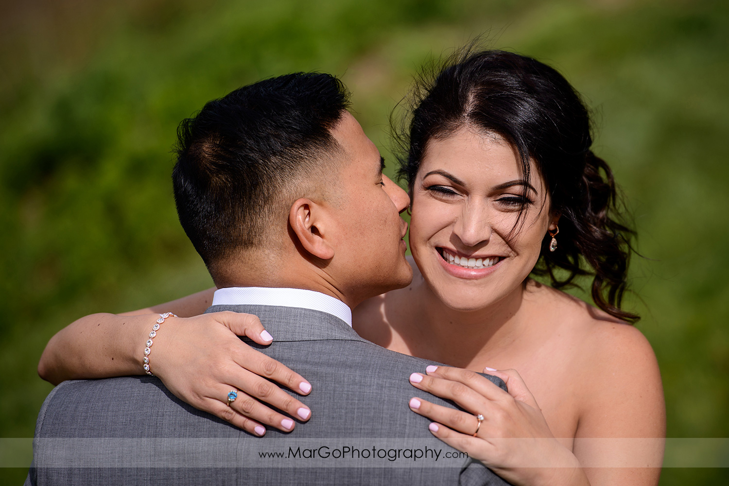 groom kissing the bride during first look at Poppy Ridge Golf Course in Livermore