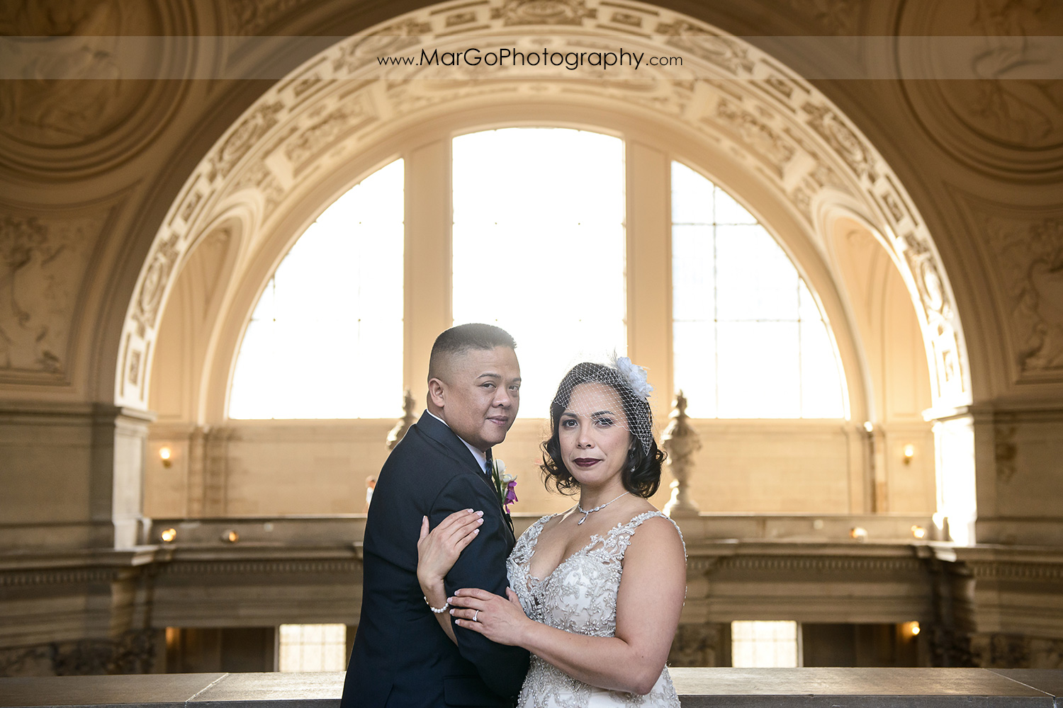 bride and groom in front of big arch window at San Francisco City Hall