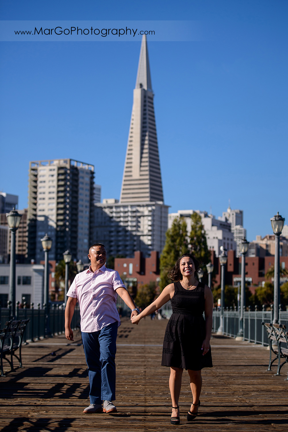 engagement session at Pier 7 in San Francisco - couple walking with the Transamerica Pyramid in the background