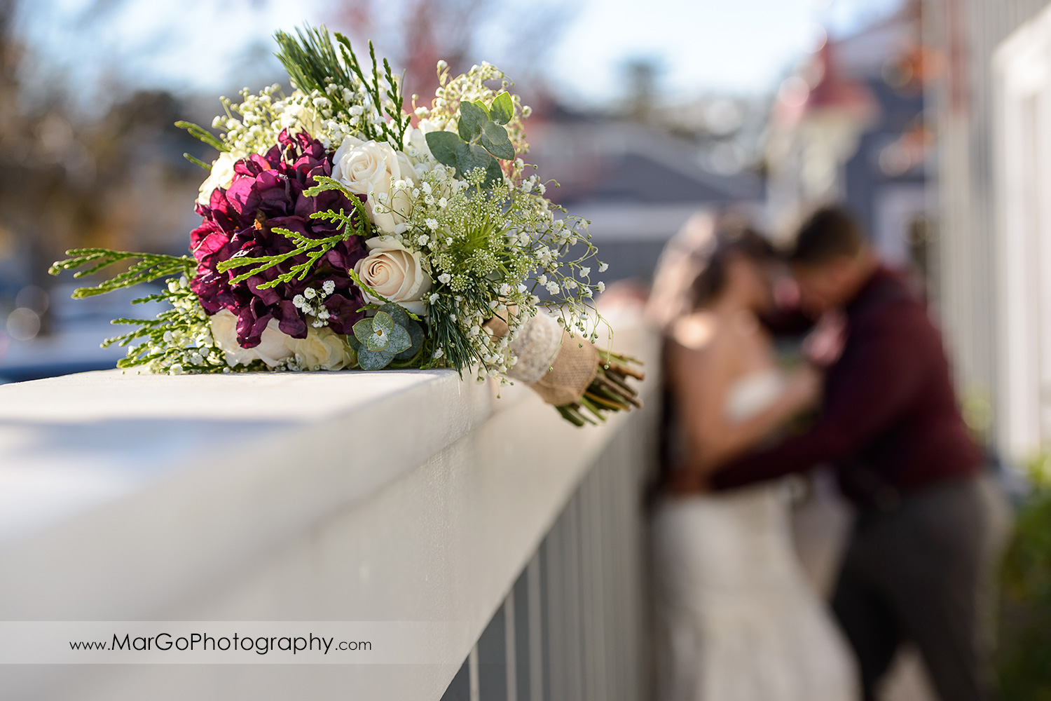 wedding bouquet with bride and groom in the background at Pleasant Hill City Hall