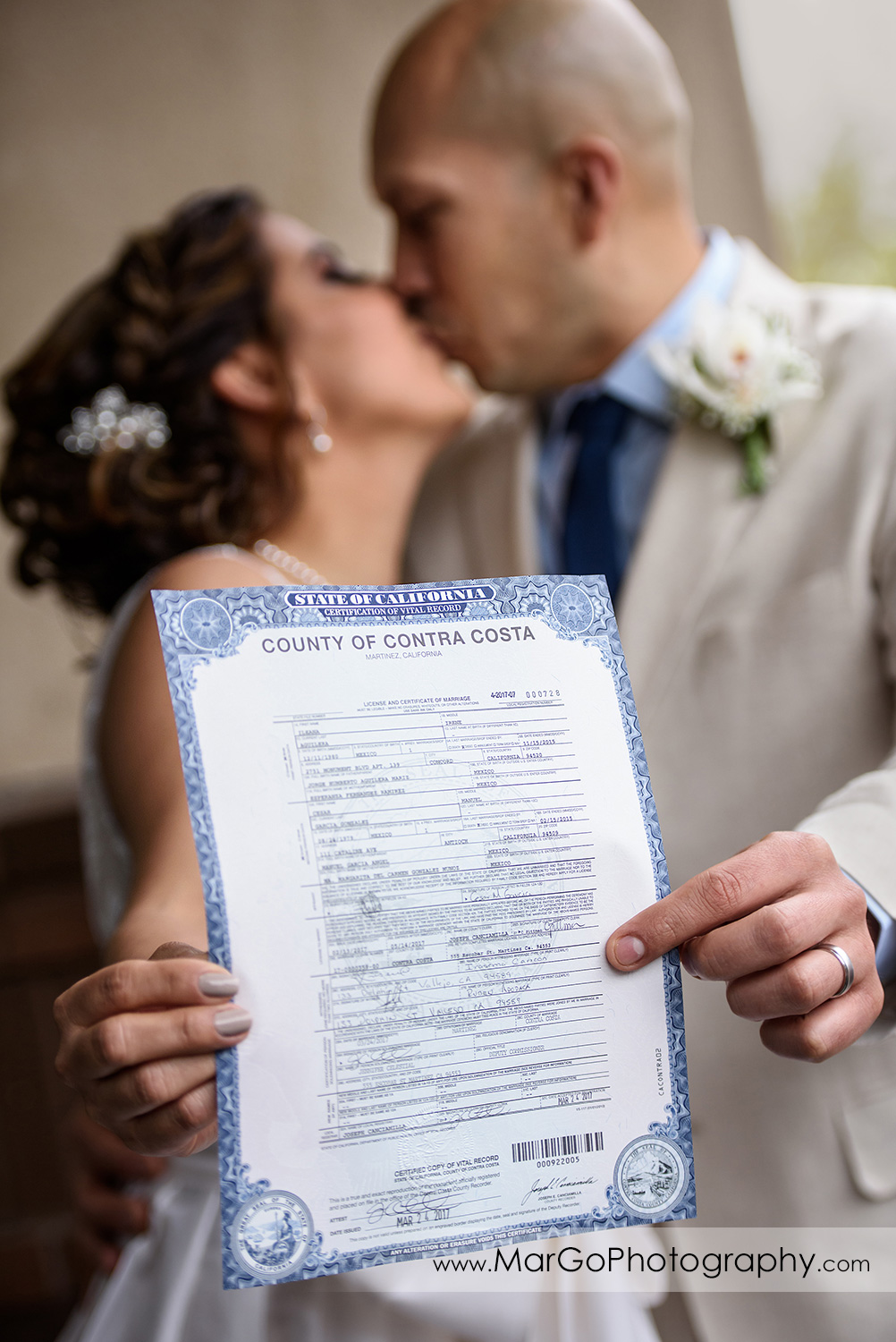 bride and groom kissing and showing marriage certificate