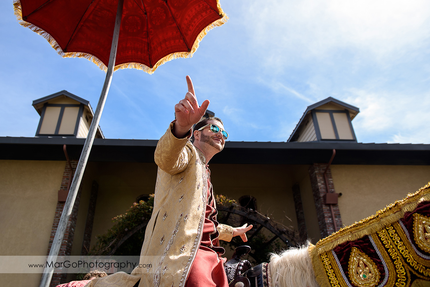 groom on white baraat horse at Palm Event Center in the Vineyard in Pleasanton