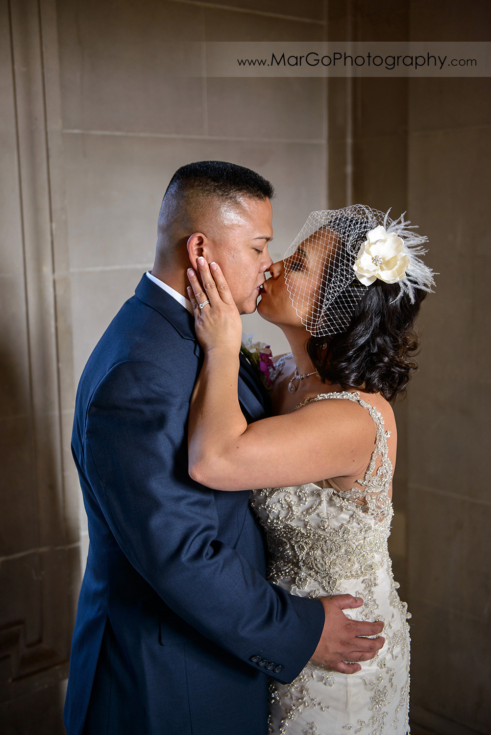bride and groom kissing at San Francisco City Hall