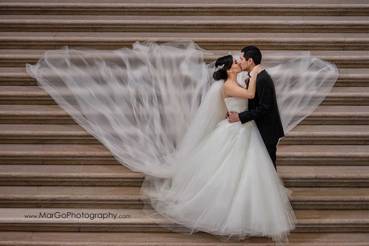 bride and groom kissing on the stairs of San Francisco City Hall