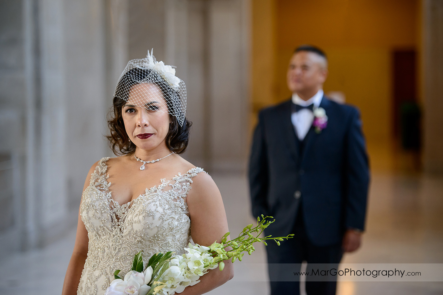 bride with the bouquet with groom in the background at San Francisco City Hall