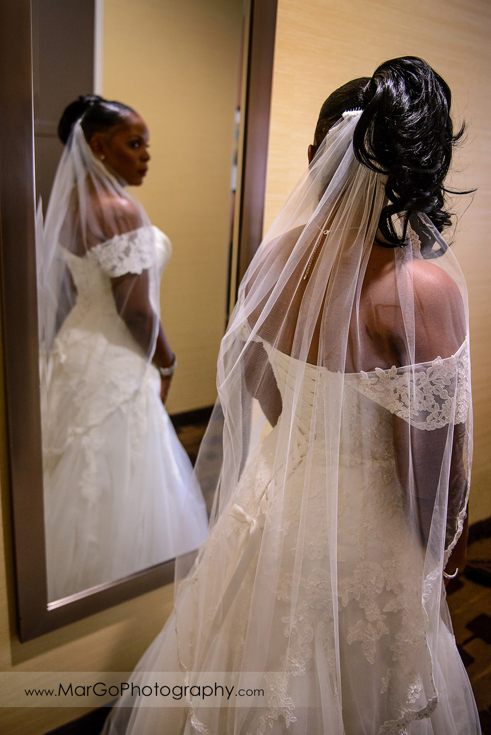 bride in a wedding dress standing in front of the mirror at Best Western Plus Delta Inn & Suites in Oakley