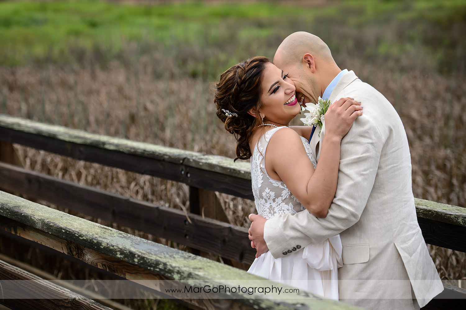 bride and groom laughing on the bridge at Martinez Regional Shoreline