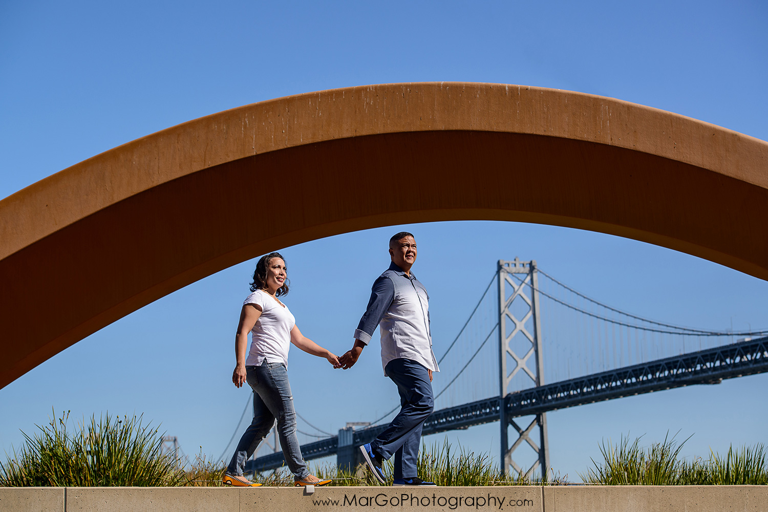 engagement session at Rincon Park in San Francisco - couple walking in front of Bow and Arrow with Bay Bridge in the background