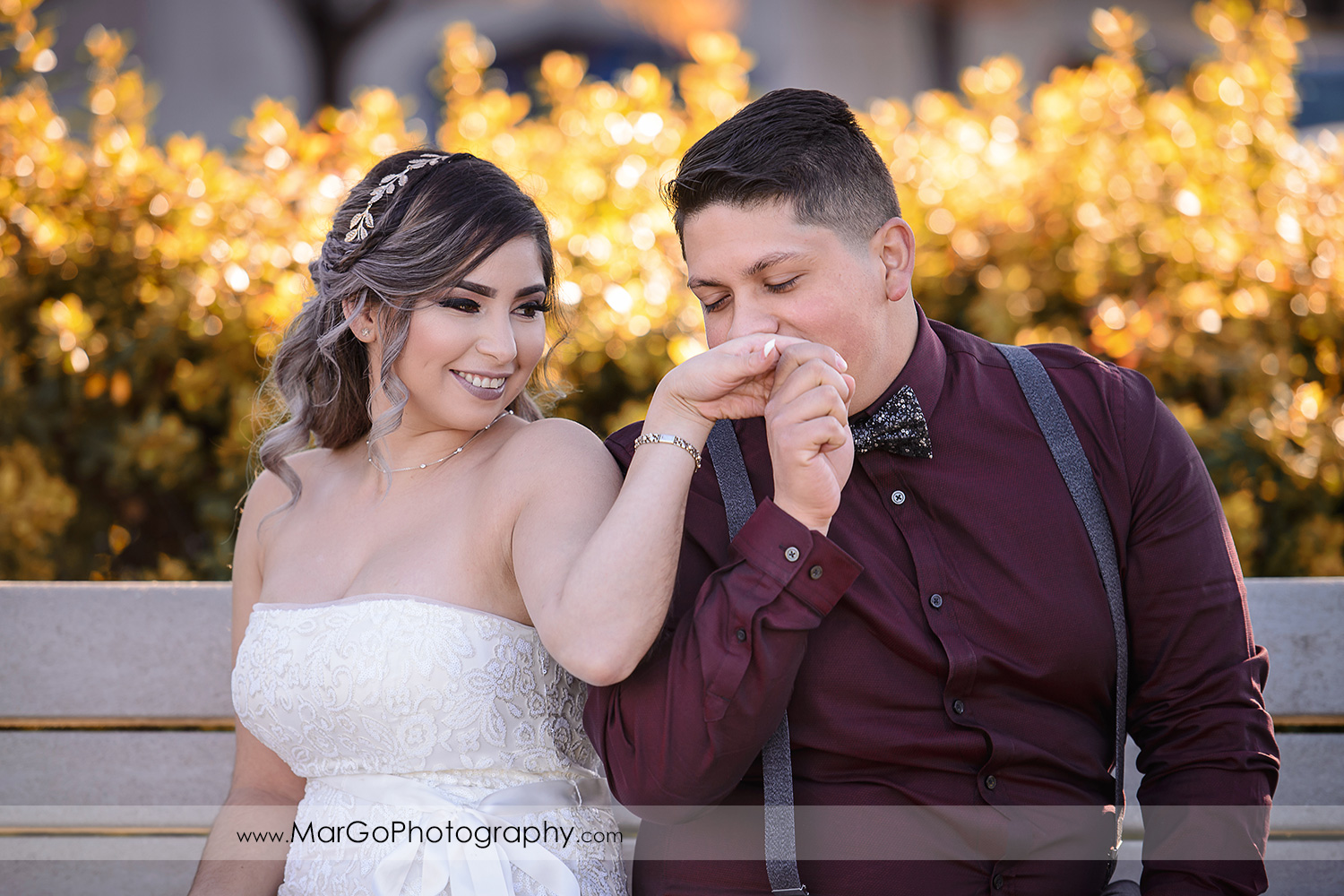 groom kissing bride's hand at Pleasant Hill City Hall