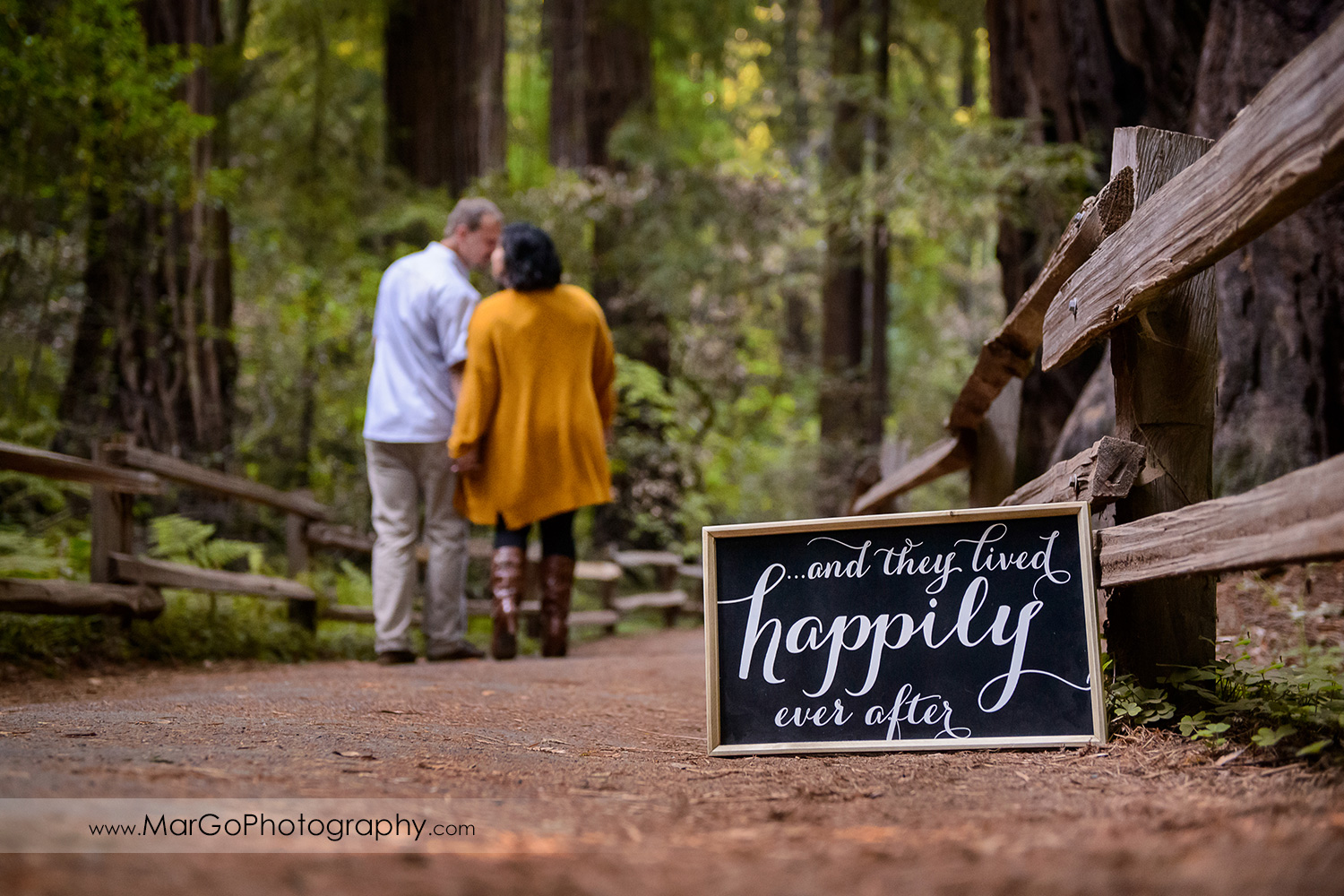 engaged couple with they lived happily ever after sign at Muir Woods National Monument