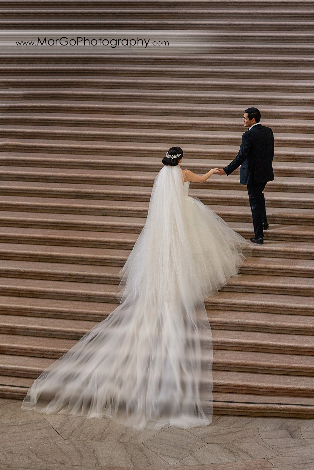bride and groom walking up the stairs of San Francisco City Hall