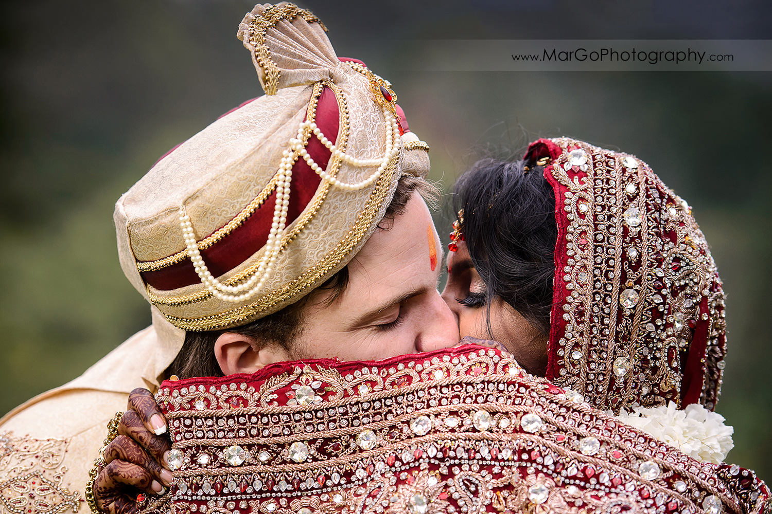 bride and groom kissing during indian wedding ceremony at Brazilian Room - Tilden Regional Park, Berkeley