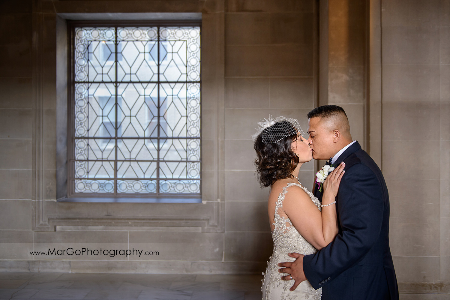 bride and groom kissing in front of stained glass window at San Francisco City Hall