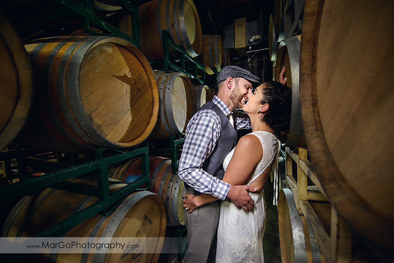 bride & groom kissing in barrel room at Picchetti Winery in Cupertino