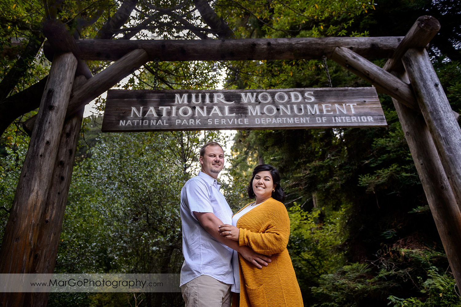 engaged couple under the sign at Muir Woods National Monument