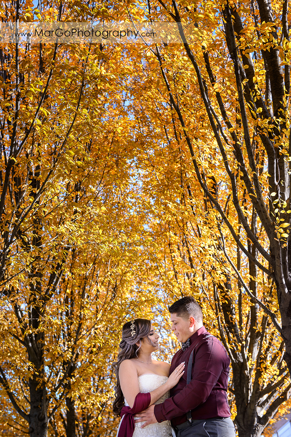 bride and groom with yellow leaves at Pleasant Hill City Hall