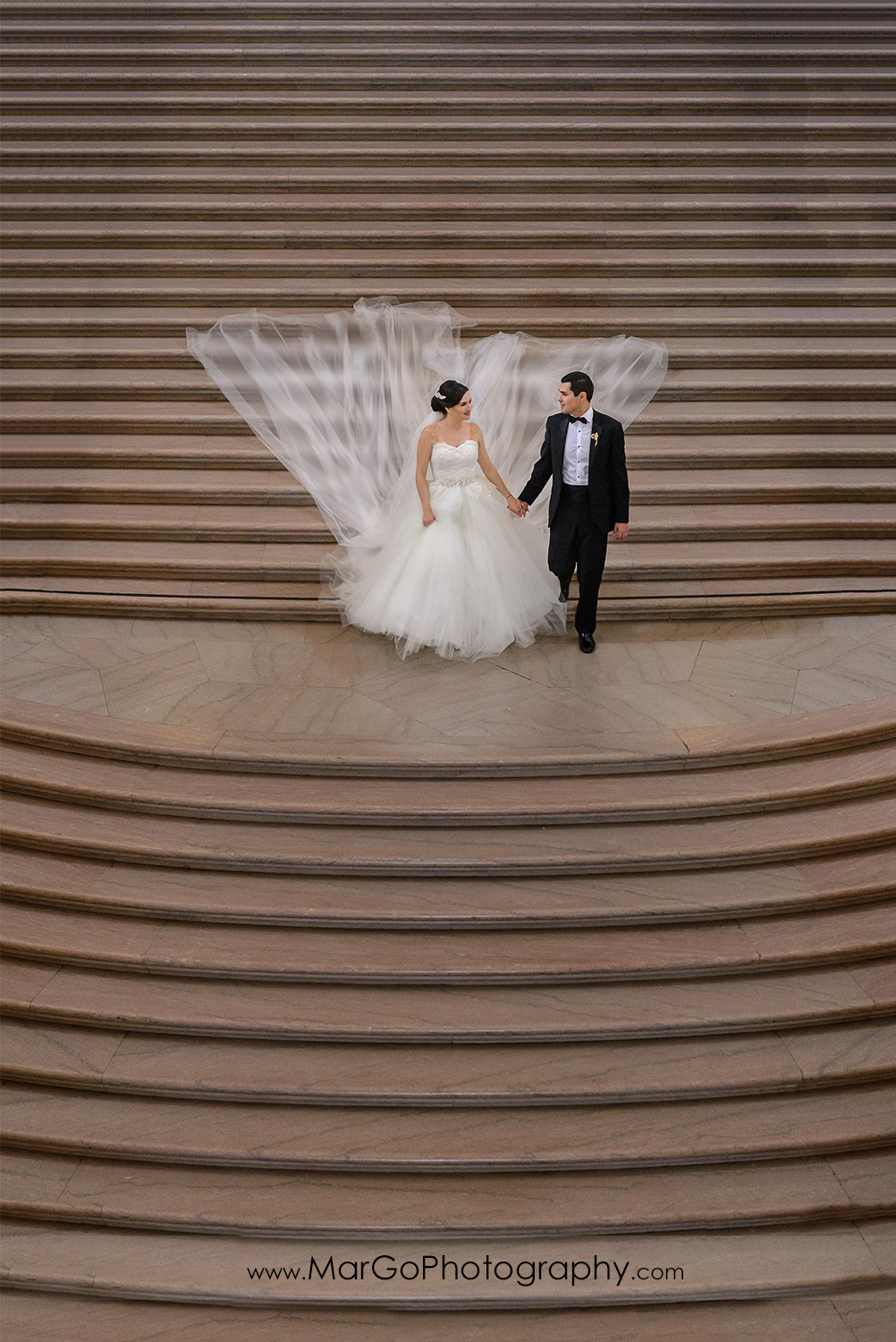 bride and groom walking down the stairs of San Francisco City Hall