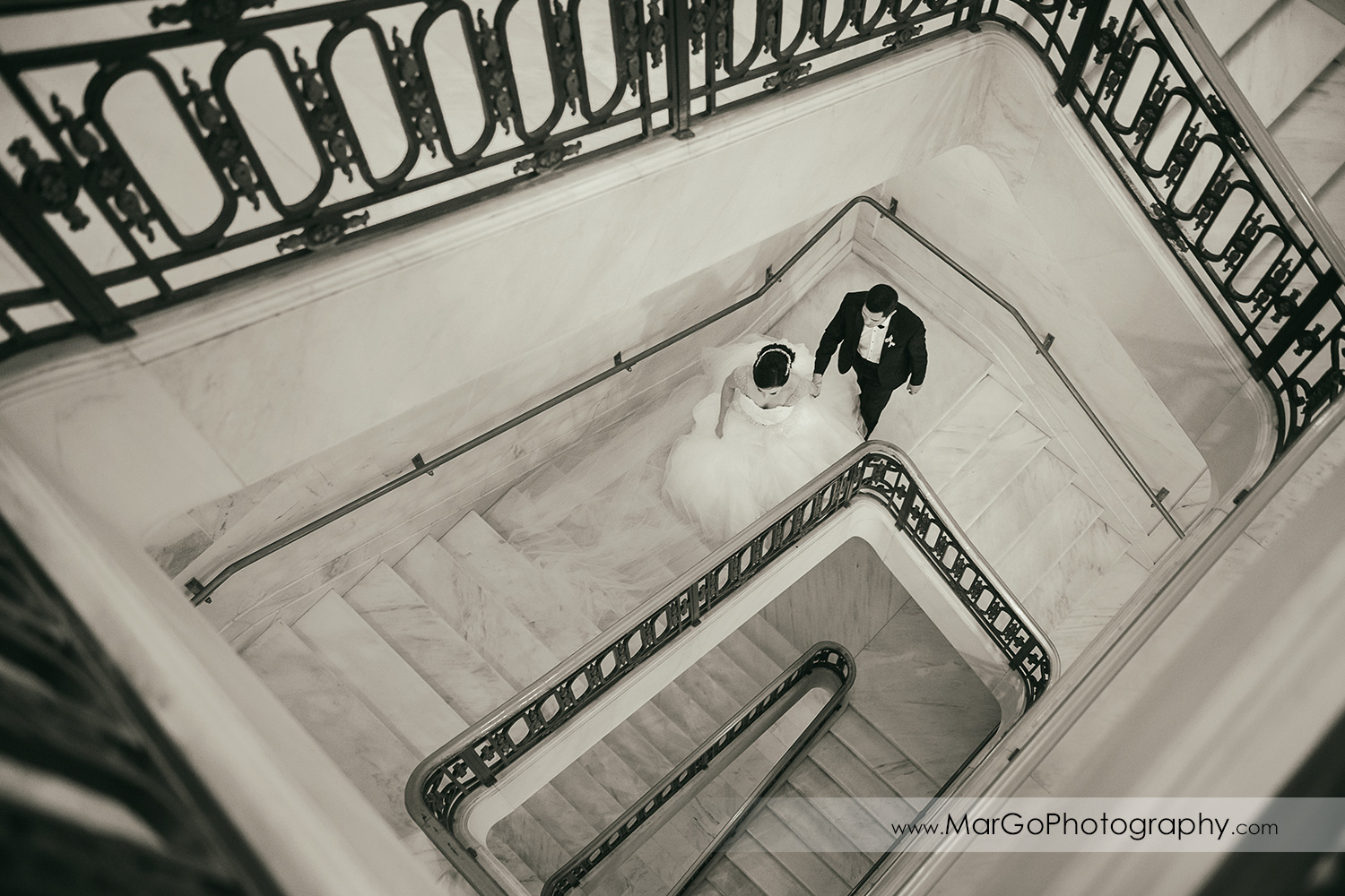b&w bride and groom walking up the stairs in San Francisco City Hall
