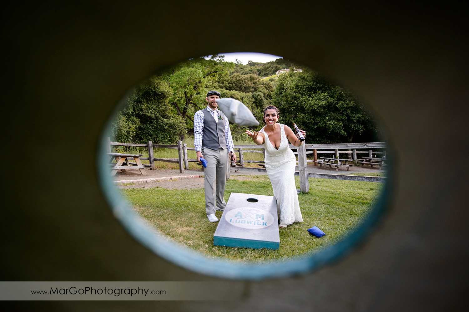 bride and groom playing cornhole game at Picchetti Winery in Cupertino